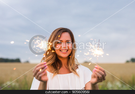 Young pretty woman having fun with a sparkler outdoors stock photo, Young pretty woman having fun with a sparkler outdoors by Satura86