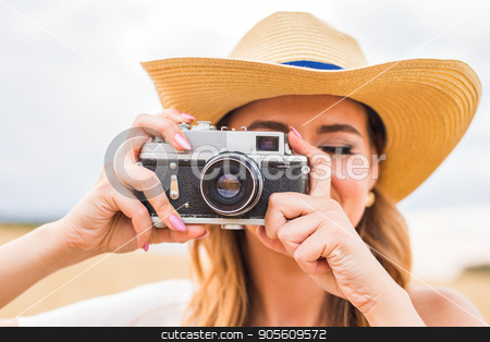 Woman holding retro camera close-up stock photo, Woman holding retro camera in the field by Satura86