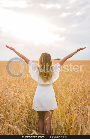 Young woman with her arms wide spread is enjoying in the sunny summer day, rear view stock photo, Young woman with her arms wide spread is enjoying in the sunny summer day, rear view by Satura86
