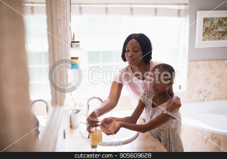 Mother assisting daughter while washing hands in bathroom stock photo, Mother assisting daughter while washing hands in bathroom at home by Wavebreak Media