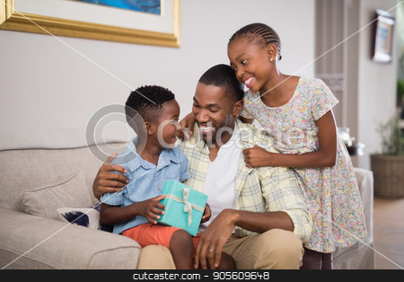 Father and children holding gift box on sofa at home stock photo, Smiling father and children holding gift box on sofa at home by Wavebreak Media