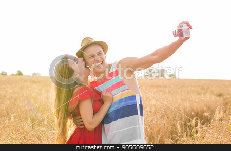 Young man and woman taking a selfie in the field stock photo, Young happy couple taking a selfie in the field by Satura86