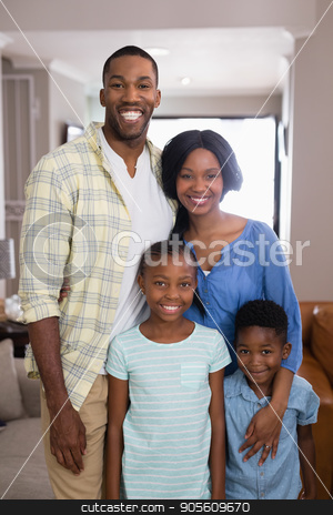 Portrait of smiling family standing at home stock photo, Portrait of smiling family standing in living room at home by Wavebreak Media