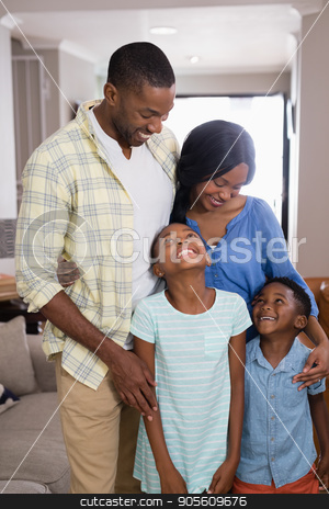 Happy parents with children standing in living room stock photo, Happy parents with children standing in living room at home by Wavebreak Media
