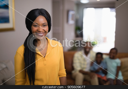 Portrait of smiling woman with family in background stock photo, Portrait of smiling woman with family in background at home by Wavebreak Media