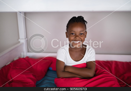 Happy girl sitting on bed at home stock photo, Portrait of happy girl sitting on bed at home by Wavebreak Media