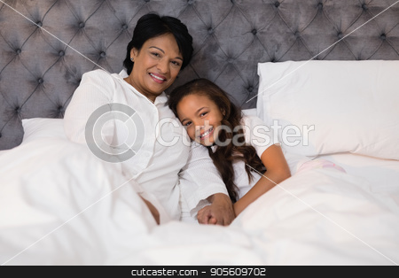 Smiling grandmother and granddaughter relaxing on bed at home stock photo, Portrait of smiling grandmother and granddaughter relaxing on bed at home by Wavebreak Media