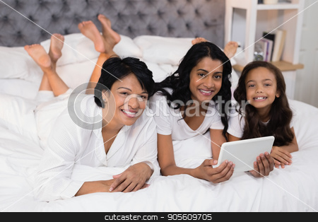 Portrait of smiling multi-generation family using digital tablet while lying on bed stock photo, Portrait of smiling multi-generation family using digital tablet while lying on bed at home by Wavebreak Media
