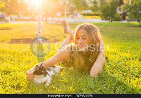young happy smiling woman with cat on natural background stock photo, young happy smiling woman with cat on natural background by Satura86