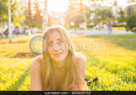Portrait of a young woman lying on the grass in sunlight stock photo, Portrait of a young woman lying on the grass by Satura86
