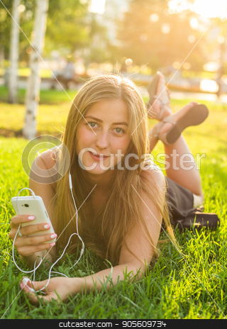 beautiful young woman listening music in the park stock photo, beautiful young woman listening music in the park by Satura86
