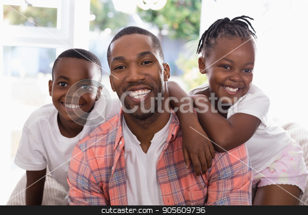 Cheerful father and children sitting on couch at home stock photo, Portrait of cheerful father and children sitting on couch at home by Wavebreak Media