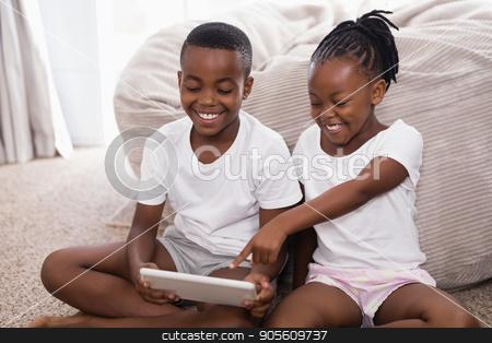 Cheerful siblings using digital tablet while sitting on rug stock photo, Cheerful siblings using digital tablet while sitting on rug at home by Wavebreak Media