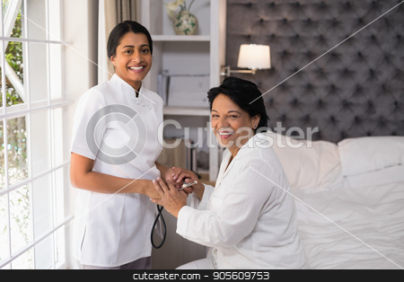 Smiling nurse and female patient at home stock photo, Portrait of smiling nurse and female patient at home by Wavebreak Media