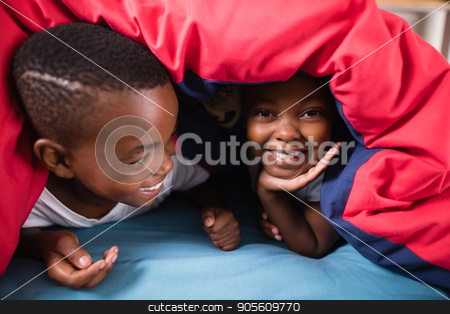 Happy siblings playing under blanket at home stock photo, Close up of happy siblings playing under blanket on bed at home by Wavebreak Media