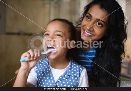 Smiling mother standing by daughter brushing teeth in bathroom stock photo, Smiling mother standing by daughter brushing teeth in bathroom at home by Wavebreak Media