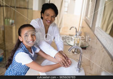 Portrait of grandmother and granddaughter washing hands stock photo, Portrait of grandmother and granddaughter washing hands at bathroom sink by Wavebreak Media