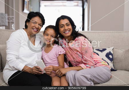 Portrait of smiling multi-generation family sitting together on sofa stock photo, Portrait of smiling multi-generation family sitting together on sofa at home by Wavebreak Media