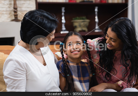 Cute smiling girl with mother and grandmother sitting at home stock photo, Cute smiling girl with mother and grandmother sitting together on sofa at home by Wavebreak Media