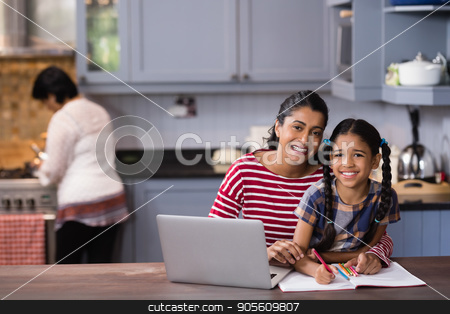 Portrait of smiling girl with mother studying in kitchen stock photo, Portrait of smiling girl with mother studying in kitchen at home by Wavebreak Media