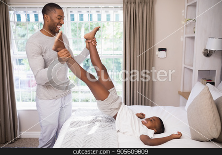 Cheerful father playing with son in bedroom stock photo, Cheerful father playing with son in bedroom at home by Wavebreak Media