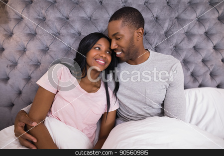 Smiling couple embracing while sitting on bed stock photo, Smiling couple embracing while sitting together on bed at home by Wavebreak Media