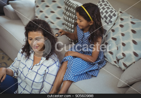 Cute daughter combing mothers hair in living room stock photo, Cute daughter combing mothers hair in living room at home by Wavebreak Media