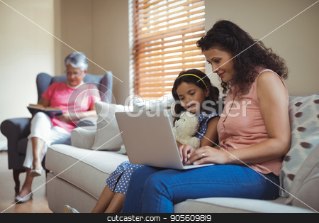 Mother and daughter using laptop in living room stock photo, Mother and daughter using laptop in living room at home by Wavebreak Media