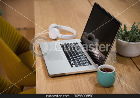 Laptop with headphones and cup on table stock photo, Laptop with headphones and cup on table in office by Wavebreak Media