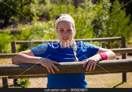 Fit woman leaning on hurdles during obstacle course training in the boot camp stock photo, Portrait of fit woman leaning on hurdles during obstacle course training in the boot camp by Wavebreak Media