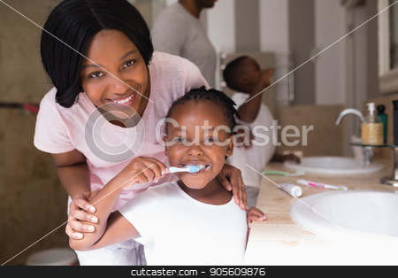 Smiling mother with daughter brushing teeth in bathroom at home stock photo, Portrait of smiling mother with daughter brushing teeth in bathroom at home by Wavebreak Media