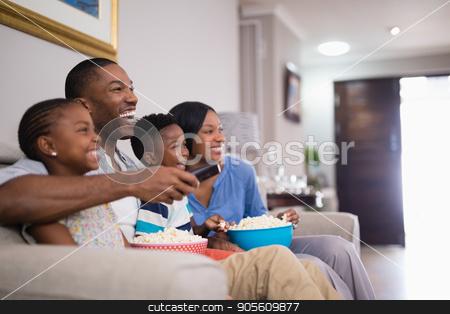 Cheerful family having popcorn while watching television stock photo, Cheerful family having popcorn while watching television at home by Wavebreak Media