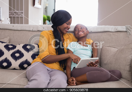 Mother and daughter using digital tablet while sitting on sofa at home stock photo, Smiling mother and daughter using digital tablet while sitting on sofa at home by Wavebreak Media