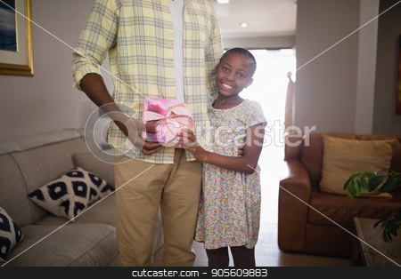 Portrait of smiling girl giving gift to father stock photo, Portrait of smiling girl giving gift to father at home by Wavebreak Media