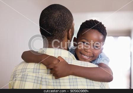 Happy boy embracing father at home stock photo, Portrait of happy boy embracing father at home by Wavebreak Media