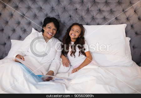 Cheerful grandmother and granddaughter resting on bed at home stock photo, Portrait of cheerful grandmother and granddaughter resting on bed at home by Wavebreak Media
