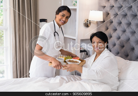 Smiling nurse serving breakfast to patient resting on bed at home stock photo, Portrait of smiling nurse serving breakfast to patient resting on bed at home by Wavebreak Media