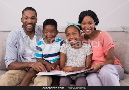 Smiling family holding magazine while sitting on sofa at home stock photo, Portrait of smiling family holding magazine while sitting on sofa at home by Wavebreak Media