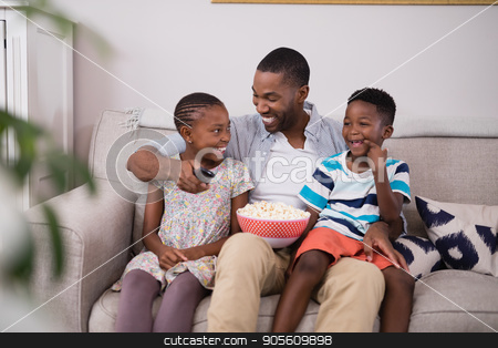 Cheerful father and children with popcorn sitting on sofa stock photo, Cheerful father and children with popcorn sitting on sofa at home by Wavebreak Media