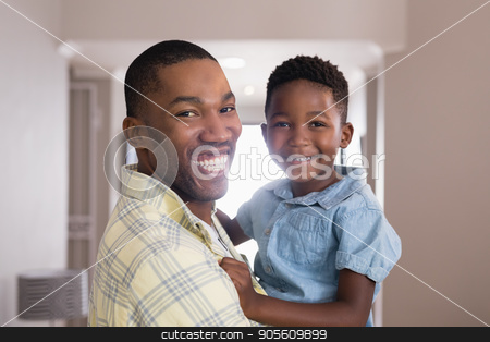 Happy father and son in living room at home stock photo, Portrait of happy father and son in living room at home by Wavebreak Media