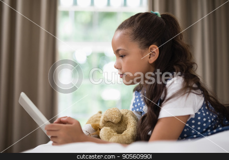 Side view of smiling girl using digital tablet while lying on bed stock photo, Side view of smiling girl using digital tablet while lying on bed at home by Wavebreak Media