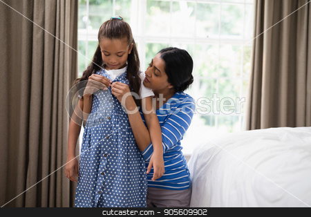 Mother helping daughter to dress up in bedroom stock photo, Mother helping daughter to dress up in bedroom at home by Wavebreak Media
