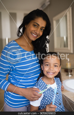 Smiling girl with mother holding toothbrushes in bathroom stock photo, Portrait of smiling girl with mother holding toothbrushes in bathroom by Wavebreak Media
