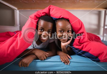 Portrait of smiling siblings lying under blanket stock photo, Portrait of smiling siblings lying under blanket on bed at home by Wavebreak Media