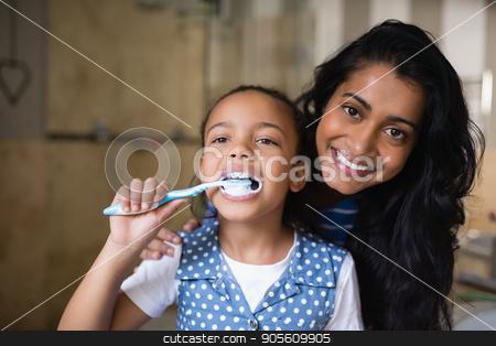 Girl brushing teeth with mother in bathroom stock photo, Close up of girl brushing teeth with mother in bathroom by Wavebreak Media