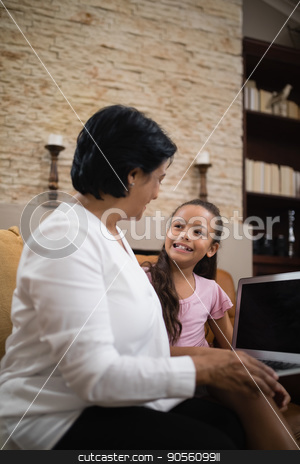 Smiling girl with grandmother holding laptop at home stock photo, Smiling girl with grandmother holding laptop while sitting on sofa at home by Wavebreak Media