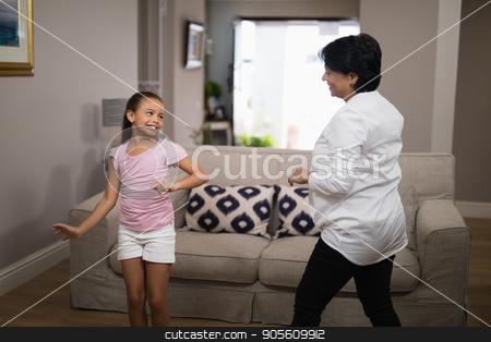 Smiling girl dancing with grandmother stock photo, Smiling girl dancing with grandmother at home by Wavebreak Media