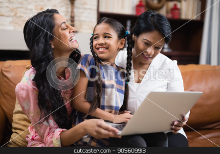 Happy multi-generation family using laptop while sitting together stock photo, Happy multi-generation family using laptop while sitting together on sofa at home by Wavebreak Media