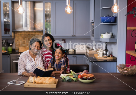 Portrait of smiling multi-generation family sitting in kitchen stock photo, Portrait of smiling multi-generation family sitting together in kitchen at home by Wavebreak Media