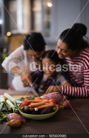 Vegetables on table against multi-generation family preparing food in kitchen stock photo, Vegetables on table against multi-generation family preparing food in kitchen at home by Wavebreak Media
